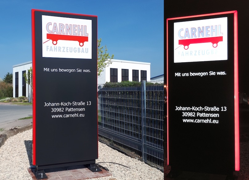 Rot-Schwarzer Werbepylon beleuchtet bei Tag und Nacht